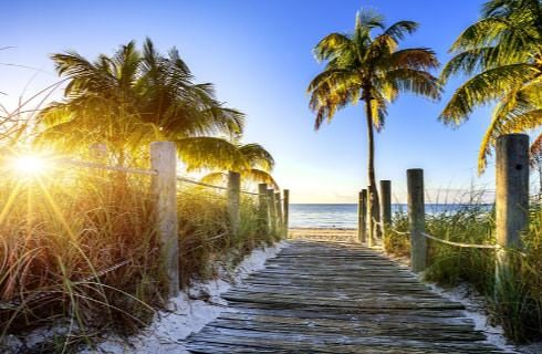 Wooden path with wooden posts and ropes leading to the beach with the sun rising in the background