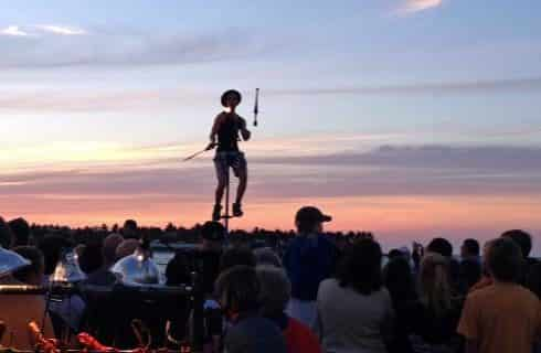Performer on a tall unicycle while juggling in a crowd of people outside