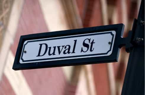 Close up view of a street sign with the words Duval St on it with a red-brick building blurred in the background