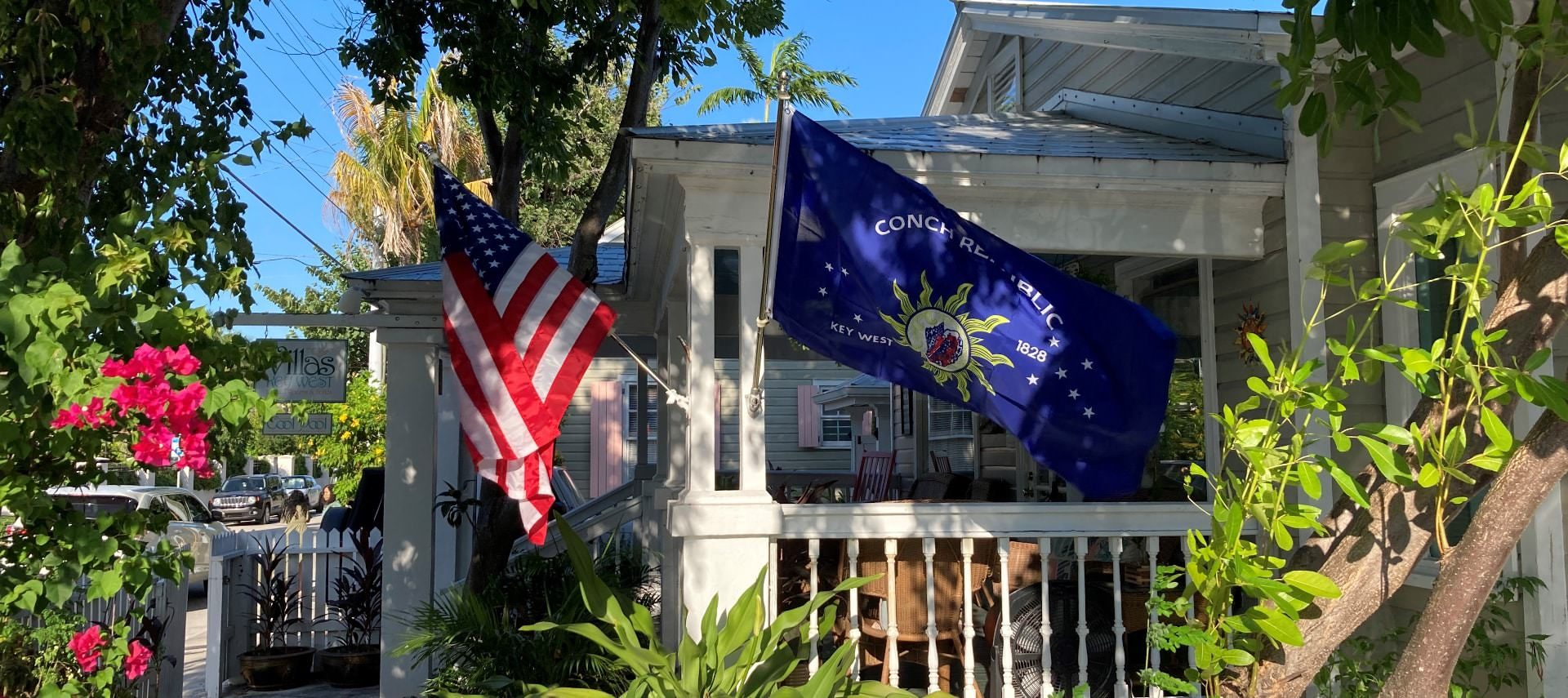 Front entrance of property with front porch, United States flag, Key West flag, and surrounded by greenery