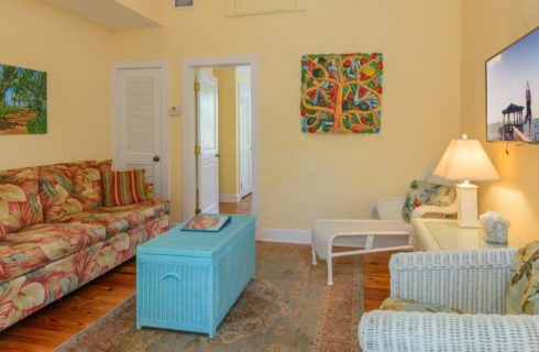 Living room with yellow walls, white trim, hardwood flooring, tropical-colored love seat, turquoise-colored wicker box, and white wicker chairs