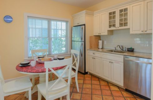 Kitchen with yellow walls, white trim, terra cotta tile flooring, white cabinets, stainless steel appliances, white table with red top, and four white chairs