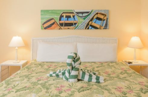 Bedroom with yellow walls, white trim, hardwood flooring, white wicker headboard, white linens, tropical comforter, and a white and green swan-shaped towel on the bed