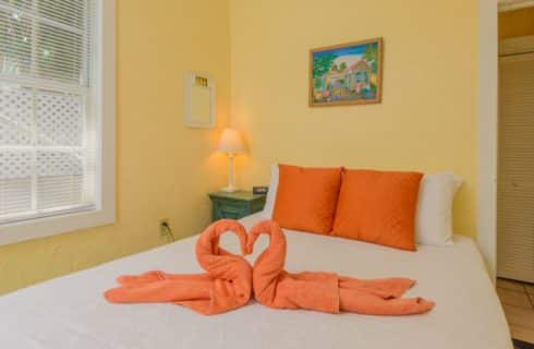 Bedroom with yellow walls, white trim, bed with white linens and orange accent pillows, and two orange swan-shaped towels on the bed