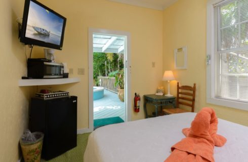 Bedroom with yellow walls, white trim, bed with white linens, two orange swan-shaped towels on the bed, flat-screen TV, mini-fridge, and view to pool