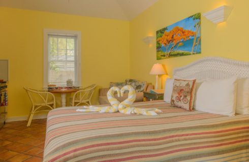 Studio with yellow walls, white trim, terra cotta tile flooring, white wicker headboard, striped blanket, two white and yellow swan-shaped towels on the bed, and kitchen with white cabinets and stainless steel appliances