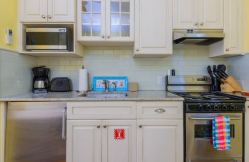 Kitchen with yellow walls, white trim, white cabinets, stainless steel appliances, and light blue tile backsplash