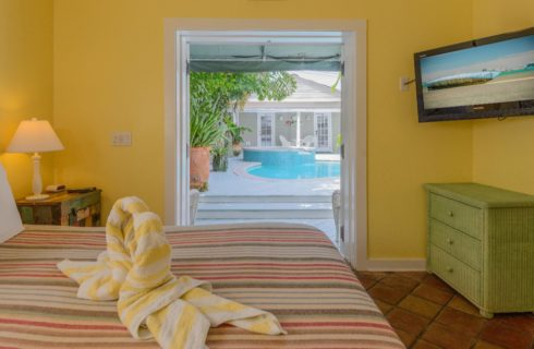 Bedroom with yellow walls, white trim, terra cotta tile flooring, white wicker headboard, striped blanket, two white and yellow swan-shaped towels on the bed, and view out to pool area