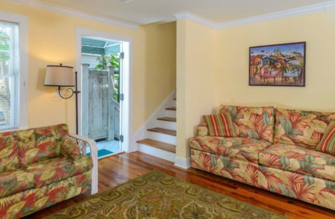 Living room with yellow walls, hardwood flooring, multiple tropical-colored love seats, and stairs to the upstairs