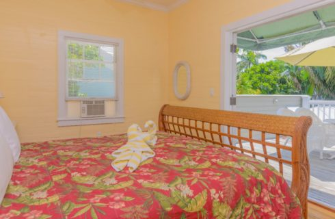 Bedroom with yellow walls, white trim, hardwood flooring, brown wicker bed, white linens, tropical comforter, and two white and yellow swan-shaped towels on the bed