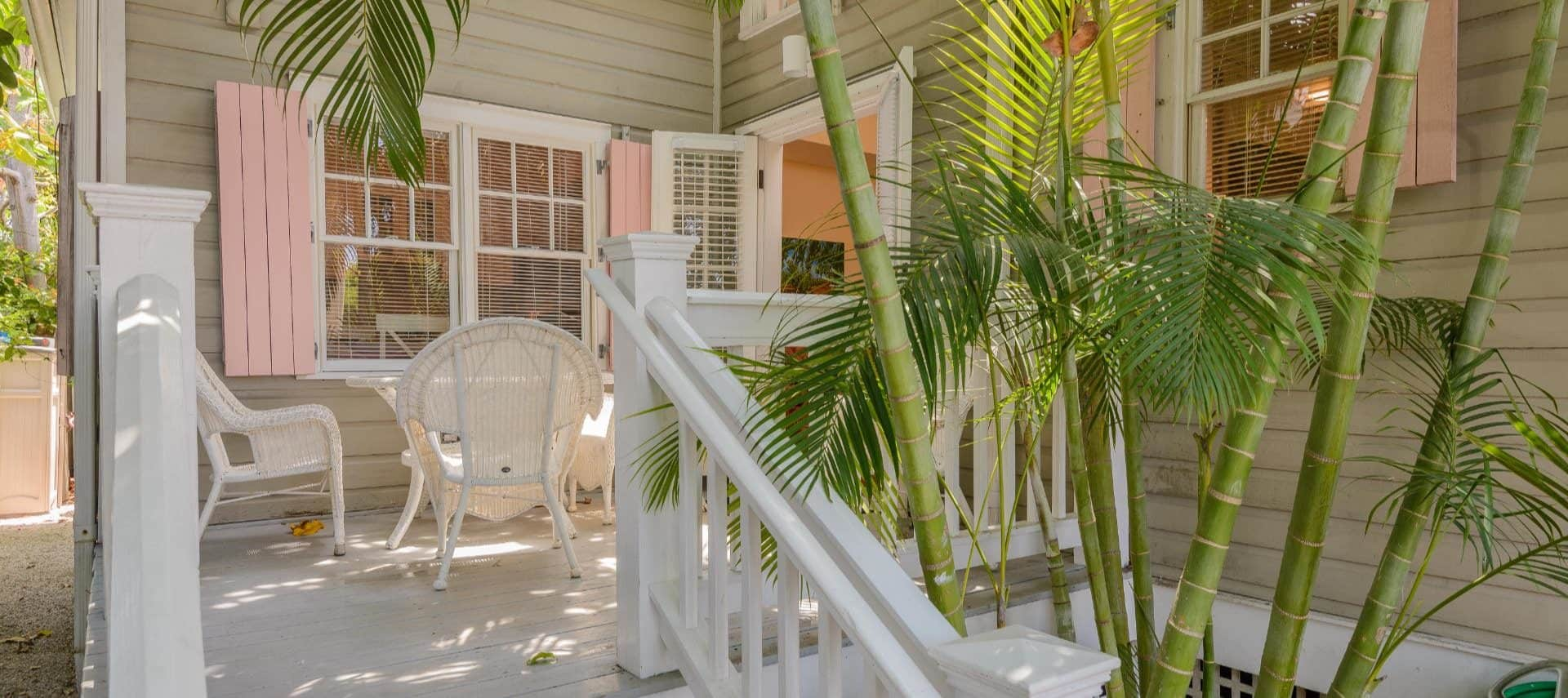 Exterior view of the property painted light tan with back porch painted white, white wicker patio furntiure, and lush greenery