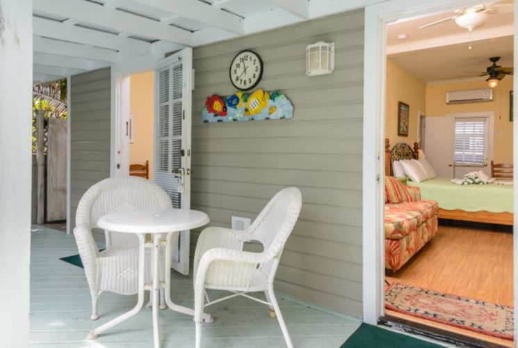 Patio with white wooden cover, white wicker chairs, small white table, and doors to bedrooms