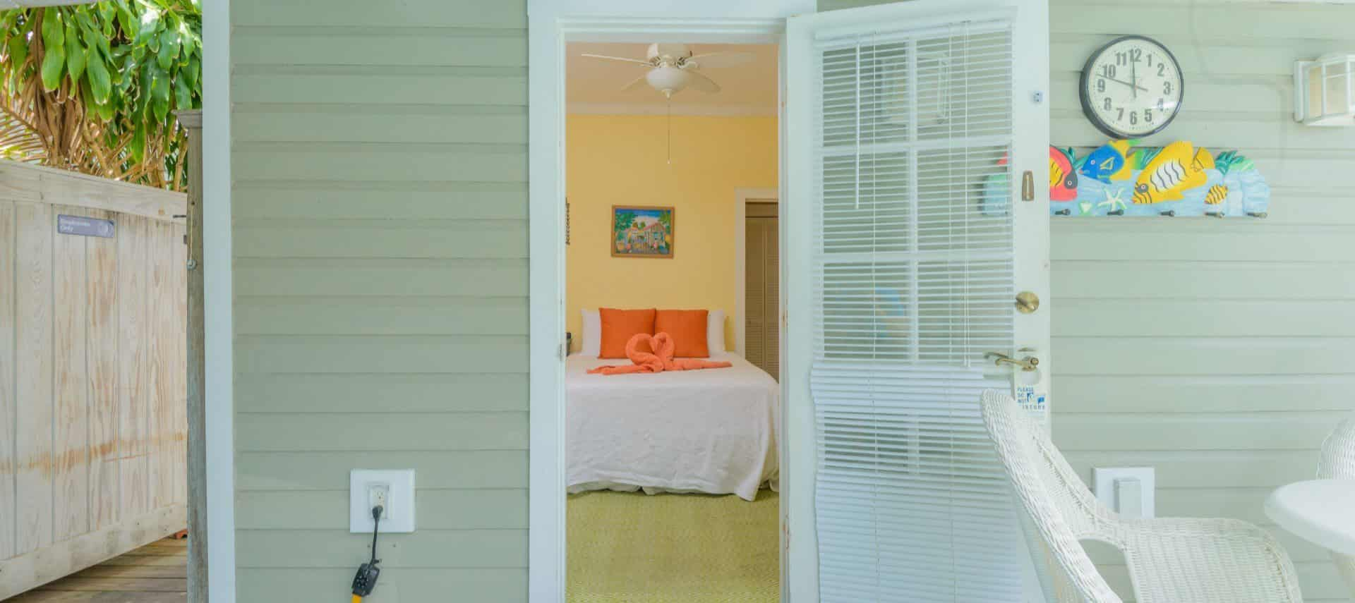 View into bedroom with yellow walls, white trim, bed with white linens and orange accent pillows, and two orange swan-shaped towels on the bed
