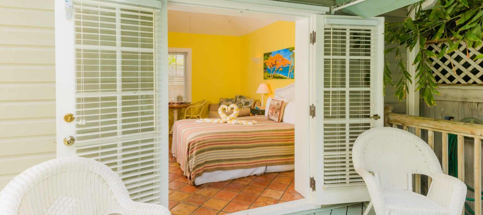 View into bedroom with yellow walls, white trim, terra cotta tile flooring, white wicker headboard, striped blanket, and two white and yellow swan-shaped towels on the bed