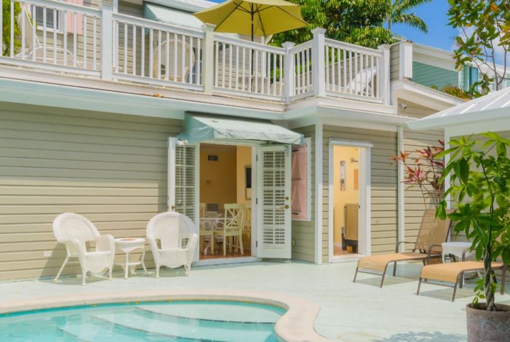 Exterior view of the property painted light tan with white trim next to large patio surrounding pool